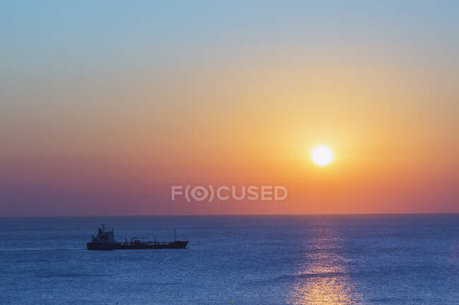 Cargo ship and sunrise over the Mediterranean sea. — Stock Photo