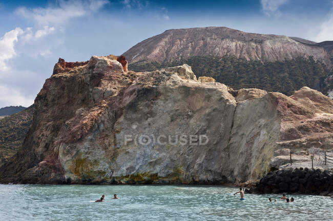 People swimming in ocean by cliffs — Photo de stock