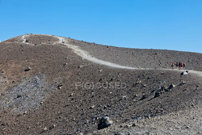 Hikers walking up rocky slope — Stock Photo