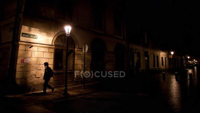 Woman walking on city street at night — Stock Photo