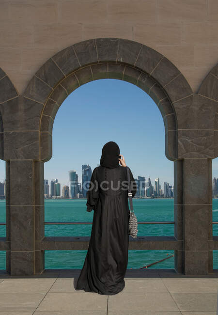 Arab woman taking pictures of skyline from the Museum of Islamic Art, Doha, Qatar — Stock Photo