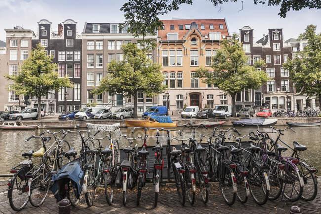 Fila de bicicletas aparcadas junto al canal, Amsterdam, Países Bajos - foto de stock
