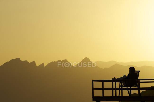 Persona silueta sentada en el balcón al atardecer, Nizwa, Omán - foto de stock