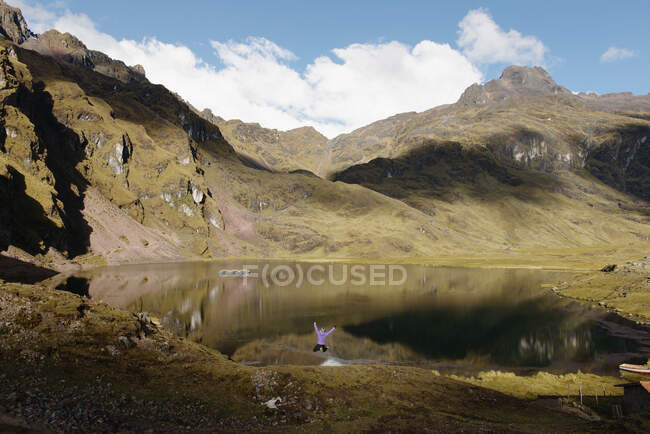 Woman jumping by lake, Lares, Peru — Stock Photo
