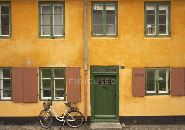 Bicicletta parcheggiata fuori dalla casa gialla, Nyboder district, Copenhagen, Danimarca — Foto stock