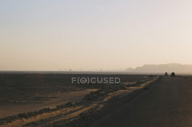 Distant view of two four wheel vehicles in desert at dusk, Egypt — Fotografia de Stock