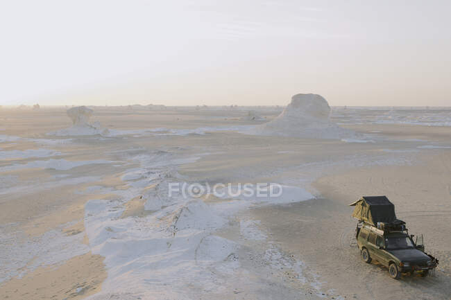 High angle view of four wheel vehicle in front of chalk rock formations in white desert, Egypt — Fotografia de Stock
