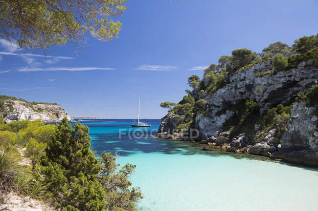 Baia costiera e vista a distanza di yacht, Cala Macarelleta, Minorca, Spagna — Foto stock