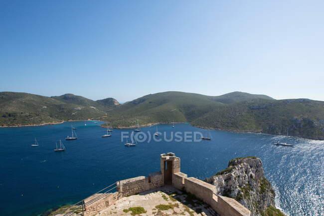 Vista de yates y mar desde el castillo sobre acantilados, Parque Nacional de Cabrera, Cabrera, Islas Baleares, España - foto de stock
