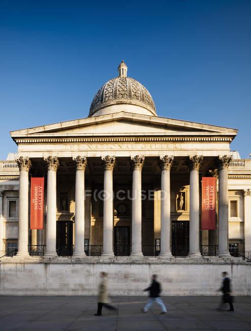 Національна галерея з невиразними ходячими людьми, сонце освітлене блакитним небом, Лондон, Велика Британія — стокове фото