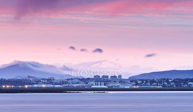 View over water of Reykjavik skyline at midnight, Iceland — Stock Photo
