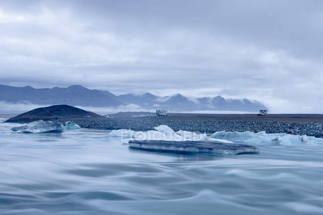 Mountain range and icebergs floating on glacial river lagoon — Stock Photo