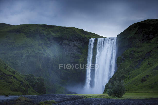 Skogafoss waterfall and grass covered mountains — Stock Photo