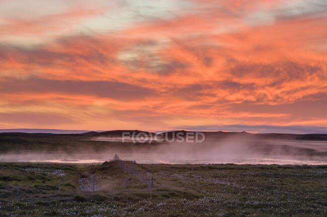 Cloud covered volcanic landscape under orange coloured dramatic sky — Stock Photo