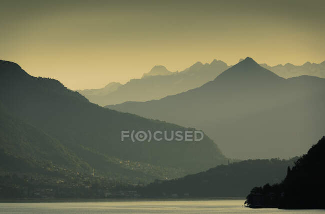 Sunrise over silhouetted mountains,  Lake Como, Italy — Stock Photo