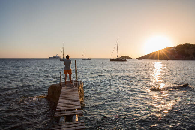 Young man looking out at sunset from old pier, Ibiza, Spain — Stock Photo