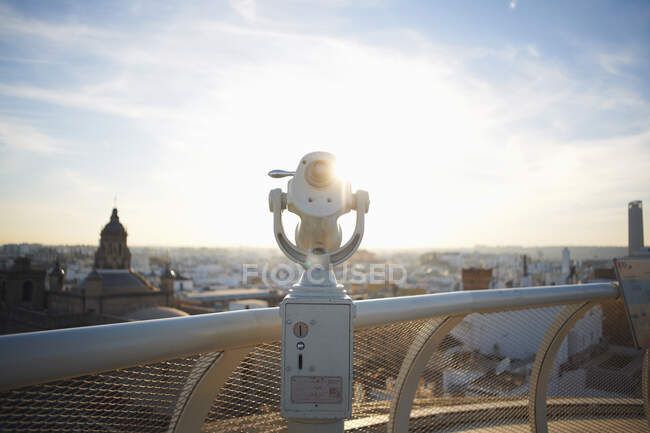 Coin operated telescope and sunlit cityscape, Seville, Andalusia — Stock Photo