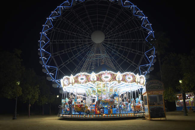 Illuminated carousel and ferris wheel at night, Seville, Andalusia — Stock Photo