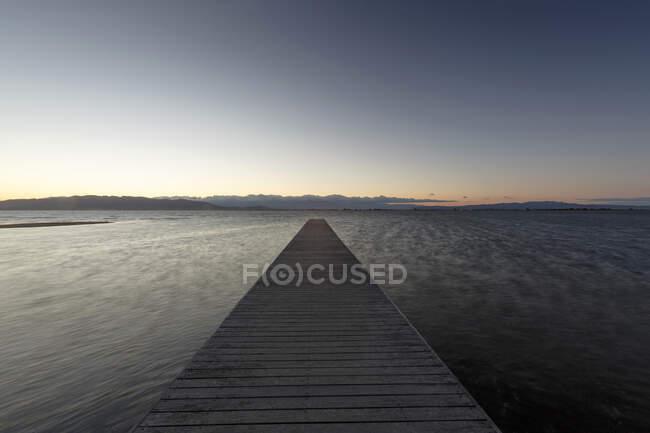 Wooden pier at dusk, Trabucador Isthmus, Alfacs Bay, Tarragona — Stock Photo
