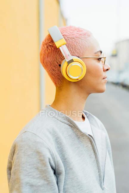 Retrato de mujer con el pelo corto de color rosa, con auriculares - foto de stock