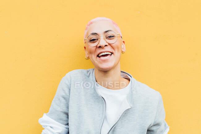 Ritratto di giovane donna felice con i capelli corti rosa, con gli occhiali — Foto stock