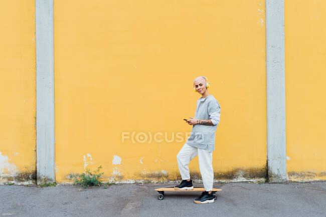 Skateboarder on board in front of yellow wall — Stock Photo