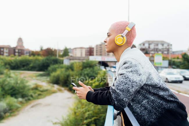 Woman on bridge, listening to music on headphones — Stock Photo