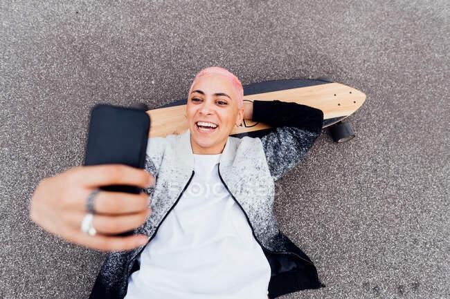 Skateboarder acostado a bordo y usando el teléfono - foto de stock