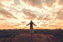 Hintere Porträt des Mannes in sportlichen Verschleiß auf Felsen mit farbenprächtigen Sonnenuntergang über Wald im Hintergrund steht — Stockfoto