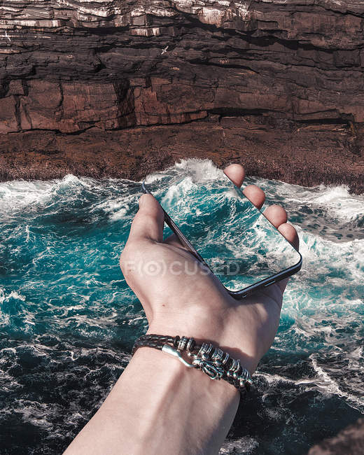 Mobile phone with impression of ocean wave — Stock Photo