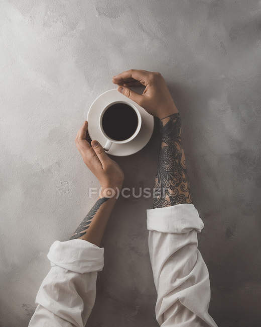 Female hands touching cup of coffee — Stock Photo