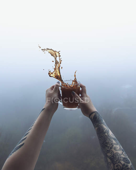 Cropped view of female hands holding cup of coffee with splash — Stock Photo