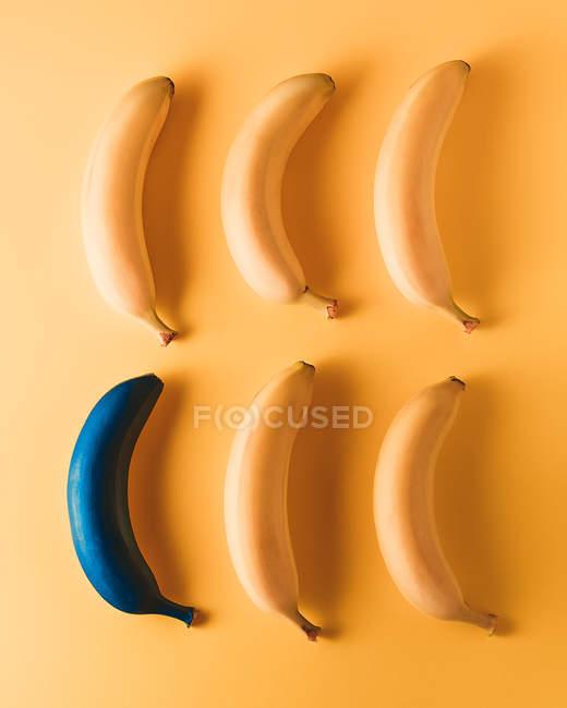 Bananen auf gelbem Hintergrund, eine mit blauer Farbe — Stockfoto