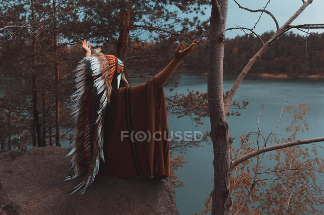 Rear portrait of woman in native American headwear sitting on stone near river with outstretched hands — Stock Photo