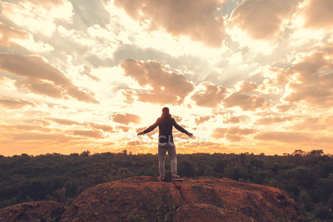 Задні портрет людина в спортивний одяг, стоячи на скелі з барвистими захід сонця над лісу на тлі — стокове фото
