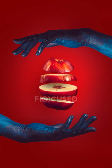 Нарезанное яблоко между двумя руками на красном фоне — стоковое фото