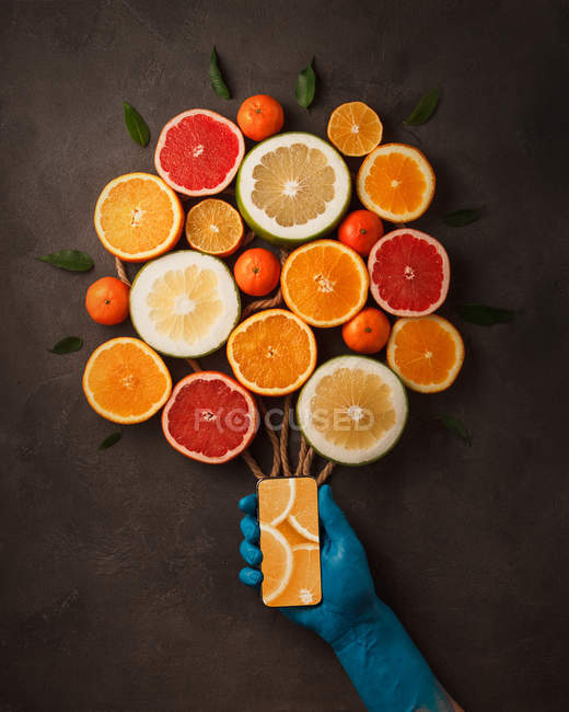 Top view of composition with human hand holding smartphone with citrus fruity bouquet — Stock Photo