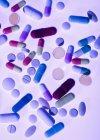 Медицинские таблетки и капсулы на белом фоне. — стоковое фото