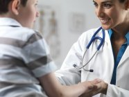 Kinderärztin spricht mit Jungen im Grundschulalter. — Stockfoto