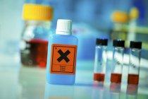 Produtos químicos em garrafas e tubos na mesa de laboratório. — Fotografia de Stock