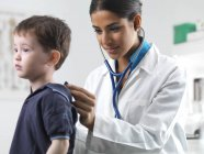 Female pediatrician using stethoscope on preschooler boy. — Photo de stock