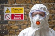 Trabalhador vestindo roupas protetoras, máscara facial e óculos de segurança . — Fotografia de Stock