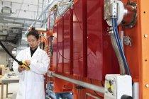 Technicien travaillant avec panneau de commande dans l'usine de production . — Photo de stock