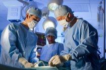 Equipe cirúrgica em máscaras faciais trabalhando em sala de operações . — Fotografia de Stock