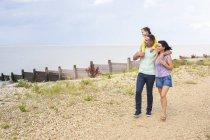 Отец дает дочь контрейлерных на пляже с матерью — стоковое фото
