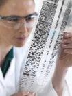 Femme scientifique regardant l'autoradiogramme ADN . — Photo de stock