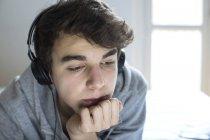 Giovane uomo che utilizza le cuffie con mano sul mento . — Foto stock