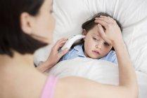 Madre tomando temperatura hija con la mano y el dispositivo en la cama . - foto de stock