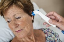 Infirmière prenant à la main la température du patient avec thermomètre numérique . — Photo de stock