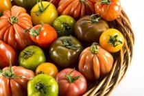 Heritage tomatoes in basket on white. — Stock Photo